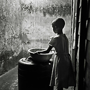 A house girl fetch the rain water dropped from the roof in Goma, Democratic Republic of the Congo.