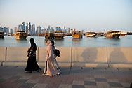 Three Arab women walk at sunset along the corniche in Doha, Qatar