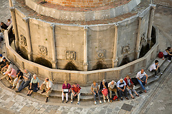 Europe, Croatia, Dalmatia, Dubrovnik.  Tourists sitting by the Big Fountain of Onofrio (15th century).  The historic center of Dubrovnik is a UNESCO World Heritage site. NMR