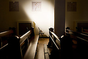 Empty pews and strong daylight shining into the 1930s built St. Lawrence's Catholic church in Feltham, London.