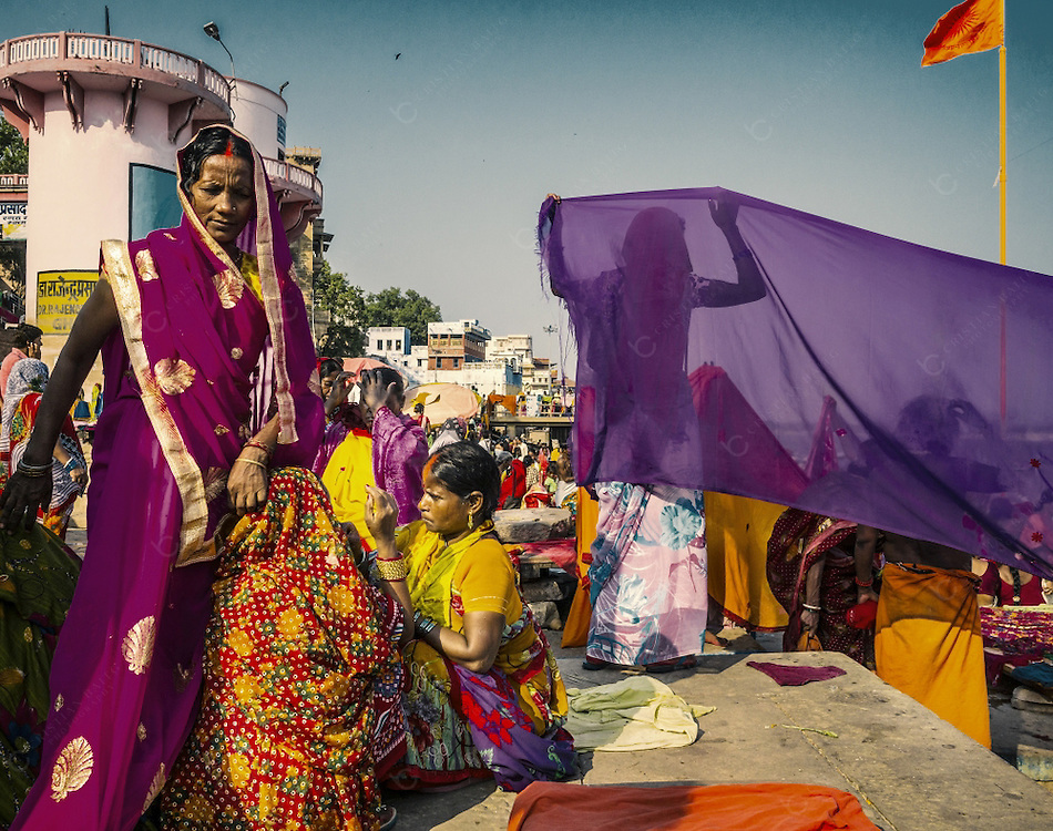 Varanasi, India - October 05, 2015: Pilgrims in Dashashwamedh Ghat in Varanasi . Many women are hanging their wet saris to dry off after bathing in the sacred Ganges river This is one of the oldest inhabited cities in the world and also the holiest of the seven sacred cities in Hinduism and Jainism and so the most important pilgrimage place for hindus.