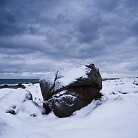 Snow covered boulder on coast, near Kvalness, Lofoten islands, Norway