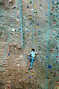 Boy scaling an indoor rock climbing wall. Atlanta, Georgia