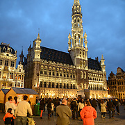 Visitors to the Grand Place, Brussels, at night, with the Town Hall (Hotel de Ville) in the background with with the tall tower. Originally the city's central market place, the Grand-Place is now a UNESCO World Heritage site. Ornate buildings line the square, including guildhalls, the Brussels Town Hall, and the Breadhouse, and seven cobbelstone streets feed into it.