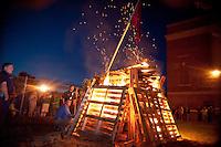 Principal Steven Beals lights the bonfire to kick off Laconia High School's Homecoming festivities Thursday evening.  (Karen Bobotas/for the Laconia Daily Sun)