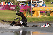 Thailand's Arinadtha Chavatanont and Boleybawn Prince fall during the equestrian's eventing team and individual cross country during the Tokyo 2020 Olympic Games at the Sea Forest Cross Country Course in Tokyo on August 1, 2021. (Photo by Yuki IWAMURA / AFP)