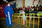 Male wrestler in blue gown making his entrace as little girl looks on from behind a barrier. Lucha Libre wrestling origniated in Mexico, but is popular in other latin Amercian countries, including in La Paz / El Alto, Bolivia. Male and female fighters participate in the theatrical staged fights to an adoring crowd of locals and foreigners alike.
