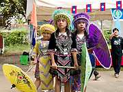 Three young Hmong ethnic minority girls wearing traditional costumes and holding decorative umbrellas before their dance performance at the Women's International Group (WIG) bazaar, Vientiane, Lao PDR. The WIG Bazaar is a charity event aiming to raise funds for projects benefitting Lao women and children.