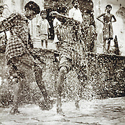 Children playing football in flooded streets, Rajahstan, India