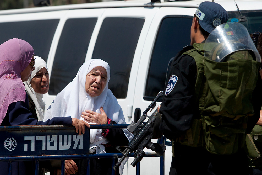 Palestinian women plead to an Israeli Border Police officer to allow them to pass, as Muslims make their way through Jerusalem's Old City to attend prayers at the Al Aqsa Mosque on the first Friday of the Muslim holy month of Ramadan, on August 13, 2010.