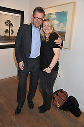 CHARLIE PHILLIPS and LAURA LOPES at a private view of photographs by various photographers entitled 'From The Road' held at Eleven, 11 Eccleston Street, London SW1 on 19th January 2012.