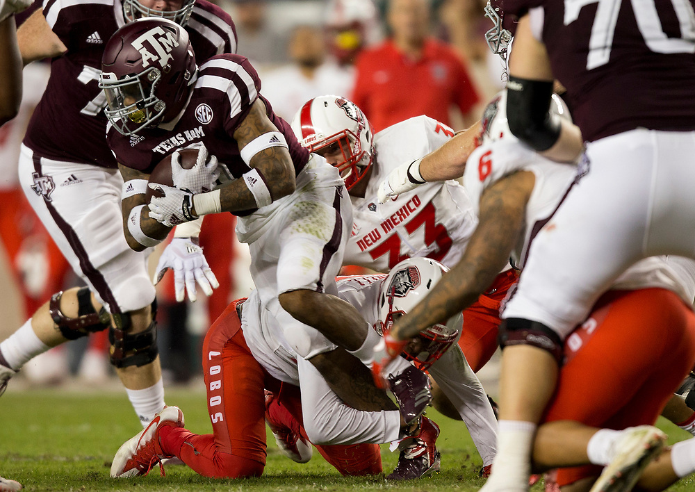 Texas A&M running back Trayveon Williams (5) breaks away from a pile of New Mexico defenders to pick up yards during the first quarter of an NCAA college football game on Saturday, Nov. 11, 2017, in College Station, Texas. (AP Photo/Sam Craft)