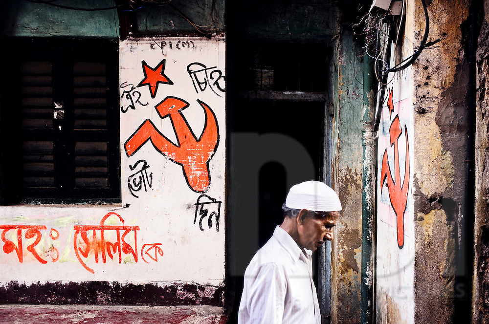 A man walks in front of a wall painted with a hammer and sickle. Rajasthan, India, Asia