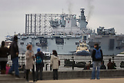 HMS Ocean (L12) of the Royal Navy edges upstream on the River Thames towards Greenwich ahead of a major security exercise in preparation for the 2012 Olympic Games. Ocean is an amphibious assault ship (or landing platform helicopter), the sole member of her class and the Royal Navy's largest ship. She then berthed at Greenwich in east London, close to the main Olympic venue where it will act as a launch pad for eight army Lynx helicopters from 661 Squadron and a base for Royal Marine snipers, able to shoot at the engines of fast-moving targets. It is the final phase of the exercise named Olympic Guardian, which began earlier this week in Weymouth, England and in the airspace over the capital. During the actual Olympics in July, Ocean will be moored in Greenwich to provide logistics support, accommodation to 9 Assault Squadron Royal Marines and a helicopter landing site. HMS (Her Majestys Ship) Ocean was constructed in the mid 90s at a cost of £234 million, the 203.4m (667 ft) long, 21,500 tonnes. .