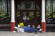 Homeless people sleeping rough in a doorway surrounded by an idillic picture of a natural forest landscape in Covent Garden in London, England, United Kingdom. Homelessness has been on the increase in the UK over the last decade, and is very visible and apparent on the streets.