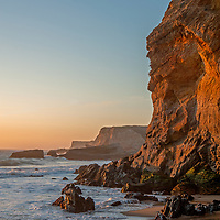 A hiker stands atop a colorful eroded cliff during sunset at Panther Beach, north of Santa Cruz, California.