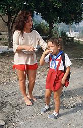 School girl wearing uniform standing in street with mother near Jibacoa; Cuba,