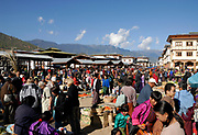 A crowd of people inspect goods on sale in the market square in Paro. Bhutanese people are in western and traditional dress. Modern concrete built buildings decorated in traditional style can be seen.  Paro, Bhutan. Druk Yul. 11 November 2007