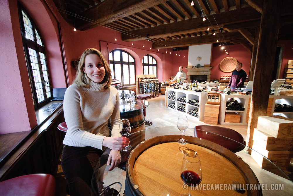 Young woman having a glass of wine in a wine shop in Beaune in Burgundy