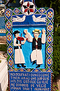 Tombstone showing a fiddler and a man doing a traditional dance,  The  Merry Cemetery ( Cimitirul Vesel ),  Săpânţa, Maramares, Northern Transylvania, Romania.  The naive folk art style of the tombstones created by woodcarver  Stan Ioan Pătraş (1909 - 1977) who created in his lifetime over 700 colourfully painted wooden tombstones with small relief portrait carvings of the deceased or with scenes depicting them at work or play or surprisingly showing the violent accident that killed them. Each tombstone has an inscription about the person, sometimes a light hearted  limerick in Romanian. .<br /> <br /> Visit our ROMANIA HISTORIC PLACXES PHOTO COLLECTIONS for more photos to download or buy as wall art prints https://funkystock.photoshelter.com/gallery-collection/Pictures-Images-of-Romania-Photos-of-Romanian-Historic-Landmark-Sites/C00001TITiQwAdS8
