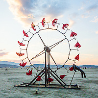Parasolvent by: Dan Benedict from: Anaheim, CA year: 2014<br /> <br /> Parasolvent is a mechanical expression of loss, release, healing and decay. Participants turn a crank to rotate a 20' tall ring of red parasols. The collapsed parasols rise up through the chest cavity of a human figure and gradually open as they climb upwards, reaching full extension at the apex, and slowly closing as they descend.<br /> This piece is a meditation on the idea that engineering and architecture can create a space or object that acts a vessel for spiritual healing; imagining something we have held inside of us, be it sickness or pain, leaving us, rising, blossoming and decaying.<br /> <br /> Contact: dan@benedictaugust.com