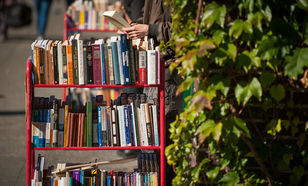 2016 October 11 - A man looks at a book outside Magus Books, University District, Seattle, WA, USA. By Richard Walker