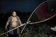 Gerard Jones, Nauru's weightlifting trainer (age 47, super class, 143 kg) hunting Noddy birds. Recording of a Noddy bird distress call is played. Noddy birds, coming back from foraging at sea, hear the call and then usually swoop down. The hunter catches them in a large net and then kill the birds by biting down on their necks. The birds, a local delicacy, are later cooked and eaten or sold 1 US$/bird, a way to compliment an income...Nauru, officially the Republic of Nauru is an island nation in Micronesia in the South Pacific.  Nauru was declared independent in 1968 and it is the world's smallest independent republic, covering just 21square kilometers..Nauru is a phosphate rock island and its economy depends almost entirely on the phosphate deposits that originate from the droppings of sea birds. Following its exploitation it briefly boasted the highest per-capita income enjoyed by any sovereign state in the world during the late 1960s and early 1970s..In the 1990s, when the phosphate reserves were partly exhausted the government resorted to unusual measures. Nauru briefly became a tax haven and illegal money laundering centre. From 2001 to 2008, it accepted aid from the Australian government in exchange for housing a Nauru detention centre, with refugees from various countries including Afghanistan and Iraq..Most necessities are imported on the island..Nauru has parliamentary system of government. It had 17 changes of administration between 1989 and 2003. In December 2007, former weight lifting medallist Marcus Stephen became the President.