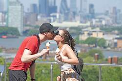 ©Licensed to London News Pictures 31/07/2020     Greenwich, UK. This young couple start their day with ice cream and a kiss in Greenwich park, Greenwich, London. Today is set to be the hottest day of the year so far with temperatures to hit 35C in parts of the UK. Photo credit: Grant Falvey/LNP