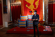 A man taking a selfie with a selfie stick while wearing a face mask in front of a replica throne used by King Henry II inside the great tower of Dover Castle, United Kingdom on the 26th of August 2020. COVID restrictions around Dover Castle mean that visitors are required to wear face coverings in certain parts of the castle. Dover Castle is a medieval castle high on the hill overlooking Dover and the English Channel, it has been a significant part of British history for the past 9 centuries and is now a UK tourist attraction run by English Heritage.