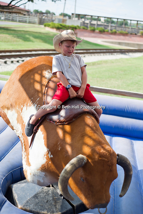Stock photography of a kid riding the mechanical bull at the Fort Worth Stock Yards sign in Fort Worth, Texas.