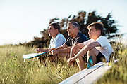 Father and sons sitting in the sand dunes with their surfboards watching the surf at St Ouen's Bay, Jersey, CI
