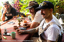 Biltwell's bike builder Rob Galen of Rouserworks, Talk Shop Podcaster Danger Dan and Gary Thomas of Ohio relax around a table at the Famous Farmhouse during Motorcycle Sherpa's Ride to the Heavens motorcycle adventure in the Himalayas of Nepal. This first day of riding took us from Kathmandu to Nuwakot. Monday, November 4, 2019. Photography ©2019 Michael Lichter.