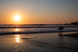 © Licensed to London News Pictures. 26/03/2020. Wadebridge, UK. A surfer on Constantine Bay beach, Cornwall during sunset this evening. British Prime Minister Boris Johnson yesterday ordered a lockdown to slow the spread of Coronavirus (COVID-19) across the country. Photo credit : Tom Nicholson/LNP