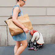 MILAN, ITALY - JULY 03:  A woman with a Gucci carrier bag walks past as  beggar on the first day of the Summer Sales in the fashion shopping area of Milan on July 3, 2010 in Milan, Italy. Milan's summer sales start today. .***Agreed Fee's Apply To All Image Use***.Marco Secchi /Xianpix. tel +44 (0) 207 1939846. e-mail ms@msecchi.com .www.marcosecchi.com