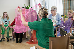 Girls with nurse and senior women doing gentle sports exercise with cloth in rest home