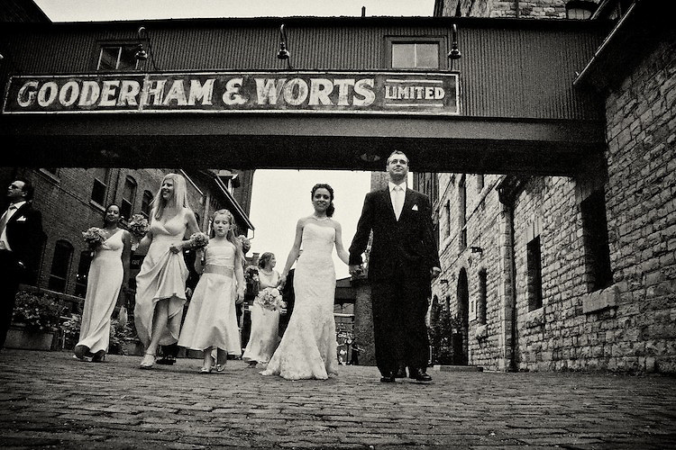 Newlyweds and their bridal party enjoy a stroll through the Distillery District, Toronto. To view Myriam and Cory's complete Wedding Gallery Collection, please visit the Client Area and log-in. You'll be able to view these and other images as a slideshow, order prints and more.<br /> <br /> © Images of a Promise by Dean Oros Photo + Design