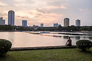 A man contemplatively sits by Giang Vo lake in Hanoi, Vietnam, Southeast Asia