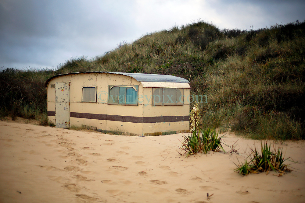 30 June 2020. South of Calais, France.<br /> Smugglers' Paradise. Deserted shacks and a deserted caravan are hidden in the sand dunes of a beach south of Calais where local police claim migrants often attempt the treacherous crossing to Great Britain. Items found in a shack and caravan including passport photos, empty water bottles, mattresses and cardboard used as bedding clearly indicate the seemingly derelict premises have recently been used. The location is reasonably remote and backs onto farmland. A gravel access road makes this a prime location for ruthless criminal gangs to drop migrants paying as much as €5,000 for a ticket on an inflatable dinghy with a small outboard motor and less for surfboards and inflatable kayaks. Local police claim it is from here and other beaches in the region that migrants often set out to make desperate and dangerous attempts to cross one of the busiest shipping lanes in the world. Migrants are crossing the English Channel (La Manche) by boat, kayak, surf board and even inflatable paddling pools as numbers seeking asylum in the UK continue to rise. <br /> Photo©; Charlie Varley/varleypix.com