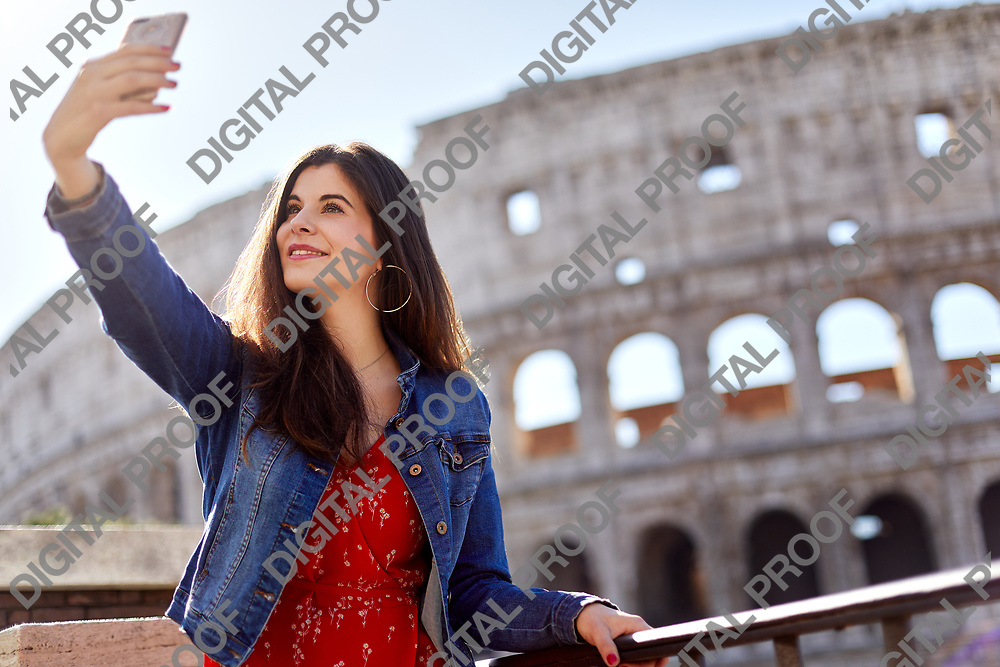 Smiling young girl takes a selfie using her phone with  the Colosseum as background during the day