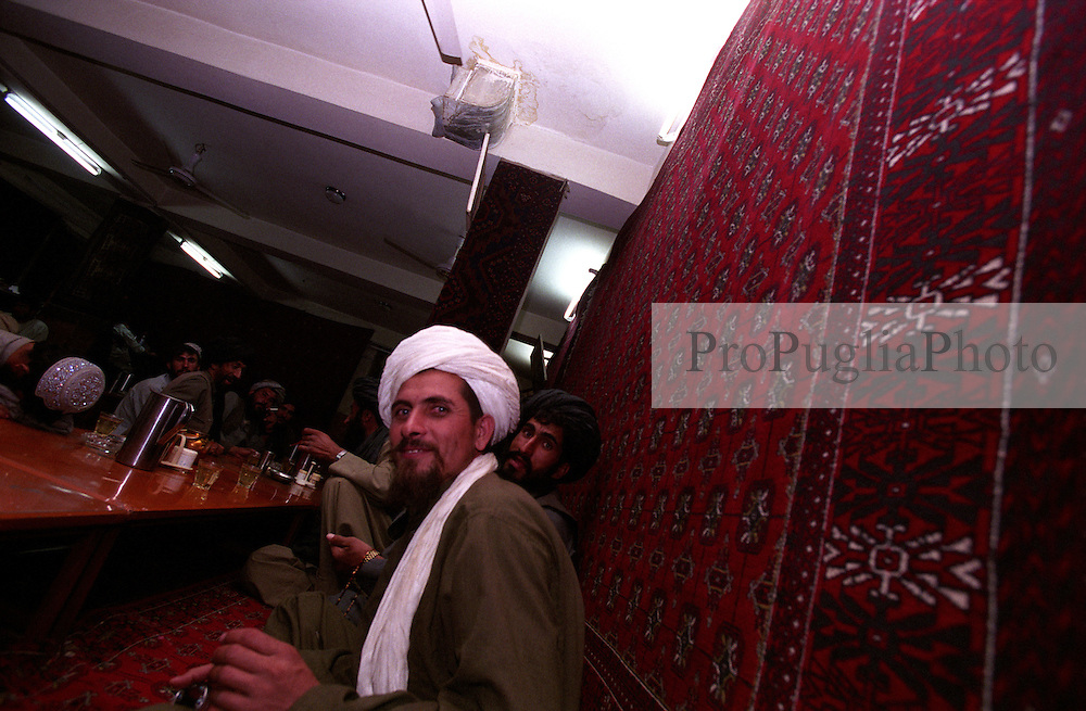 Kandahar, locals sit on the carpeted floor of a restaurant for dinner