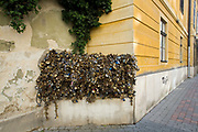 A wall and fence covered in padlocks in Pecs, Hungary. Lovers place the padlocks here as a sign of commitment in a quiet back street of the Old Town..Pecs has been chosen as the 2010 European City of Culture. The city is on the southern slopes of the Mecsek Hills and has a sub-Mediterranean climate. Settled by Romans as Sopianae, it was a significant Christian settlement. Later conquered by the Ottomans, it has important Turkish architecture.