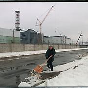 04-03-1996-Oekraine,Tsjernobyl. De kerncentrale met de sarcofaag (het donkergrijze gedeelte) een werknemer ruimt sneeuw. In dit gebied is nog een zeer hoge dosis radioactiviteit aanwezig. Kernenergie.electriciteit.<br />Foto: Sake Elzinga/Hollandse Hoogte