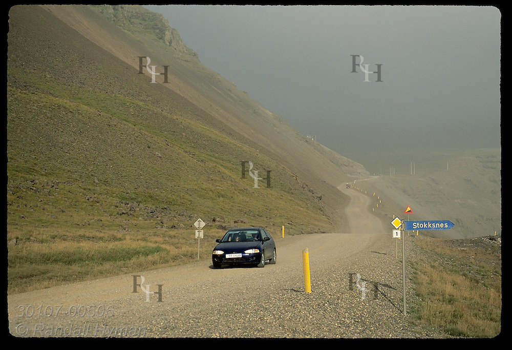 Car drives down steep gravel road on national 'ring road' highway near cape of Stokksnes; Hofn, Iceland.