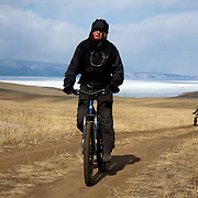 Heleen rides bicycle on Olkhon Island on Lake Baikal in Siberia, Russia, followed by Misha and Nastya. .They are a group of five people: Justin Jin (Chinese-British), Heleen van Geest (Dutch), Nastya and Misha Martynov (Russian) and their Russian guide Arkady. .They pulled their sledges 80 km across the world's deepest lake, taking a break on Olkhon, the world's forth-largest lake-bound island. They slept two nights on the ice in -15c. .Baikal, the world's largest lake by volume, contains one-fifth of the earth's fresh water and plunges to a depth of 1,637 metres..The lake is frozen from November to April, allowing people to cross by cars and lorries.
