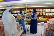Wafaa Al Haggan, assisted by one of the many foreign guest workers who do virtually all the manual labor in Kuwait, shops at her local co-op supermarket in Kuwait City. Although Kuwait imports 98 percent of its food, much of it from thousands of miles away, the choice and quality of the goods on display in supermarkets in Kuwait easily match those in European or U.S. markets, and the prices are lower. (Supporting image from the project Hungry Planet: What the World Eats.)