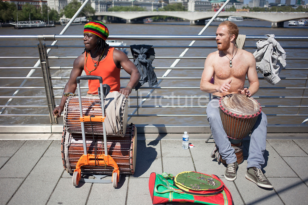 Buskers drumming on Golden Jubilee Bridge perform music to passers by. This is a popular place for busking as there is a constant and reliable footfall of people. London, UK.