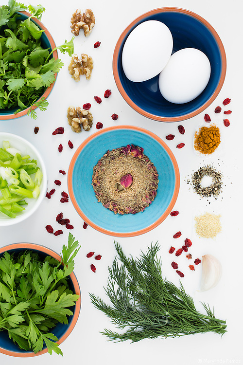 Top down view of ingredients for turmeric and herbed eggs include turmeric, fried barberries, and a middle eastern spice mix, advieh, which includes rose petals.