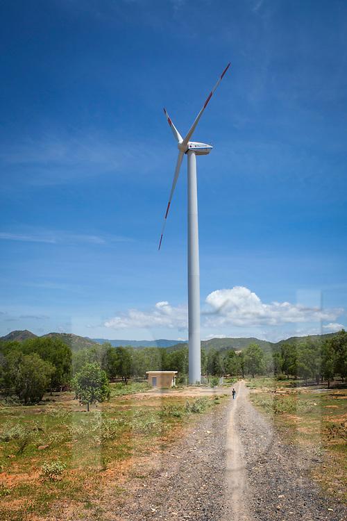 Man walking along a gravel path is dwarfed by a wind turbine on a windfarm in Ninh Thuan Province, Vietnam<br /> , Southeast Asia