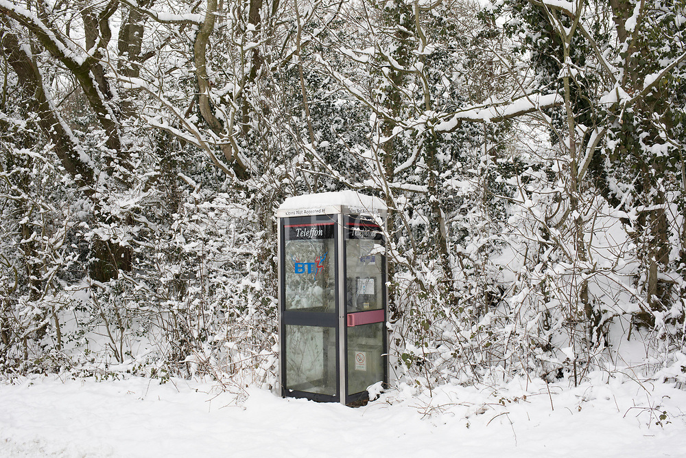 Snow scene with a covered BT telephone box in the Herefordshire countryside near Clifford, England, United Kingdom. With the UK experiencing one of its coldest winters and most snowfall in recent years. Finally, in March, the country experienced the final flurry and snowy weather sweptin from the East one last time.