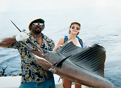 17th November, 2005. Mandeville, Louisiana. <br /> Photo courtesy Denise Leblanc. Denise photographed with a sailfish she caught off the Panamanian coast in 2000 and poses with boat Captain 'Kid,' who she claims helped save her life after an attack from a blue marlin which punctured her chest off the Panamanian coast in 2000.  Denise barely survived the horrific attack. Denise and her doctors have credited her breast implant with saving her life. <br /> Photo; Charlie Varley<br /> varleypix.com<br /> Photo courtesy; Denise Le Blanc